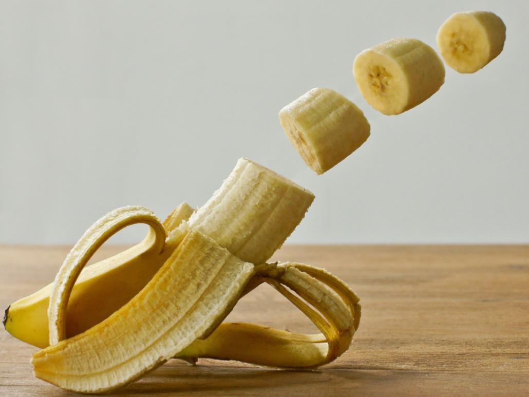 Banane mit durch die Luft fliegende Bananenscheiben